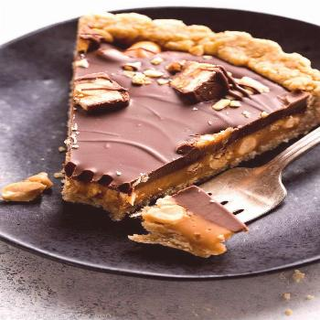 Snickers caramel tart with salted caramel, peanut crust, salty peanuts, and chocolate peanut butter